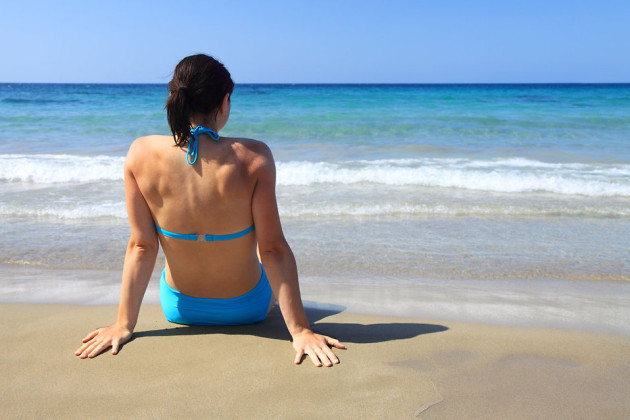 11700-a-beautiful-woman-sitting-on-the-beach-looking-at-the-ocean-pv